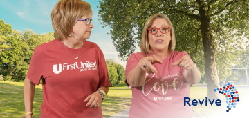 Two woman in pink shirts at the park talking