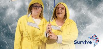 Two women in yellow raincoat standing in the rain